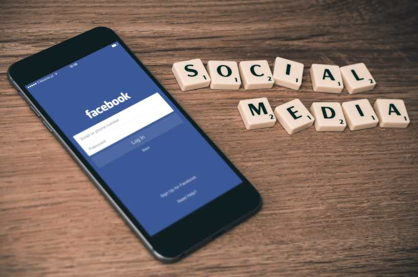 Facebook on smartphone with social media scrabble tiles